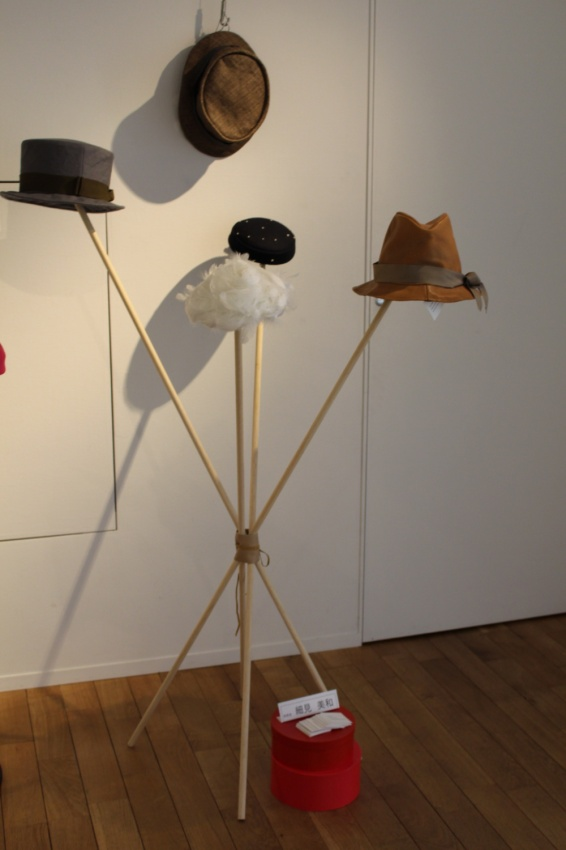 タウン系の帽子と羽根のトーク、細い棒を組んで、真ん中を皮ヒモで結びつけただけの超簡単アイディア帽子掛け