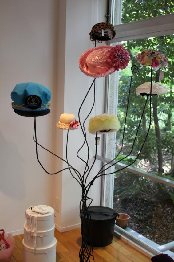 金属の木の枝風の帽子掛けにかかっているお花のような帽子たち
